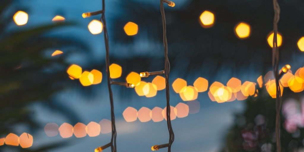 blurred light bokeh with coconut palm tree background on sunset, yellow string lights with bokeh decor in outdoor restaurant.